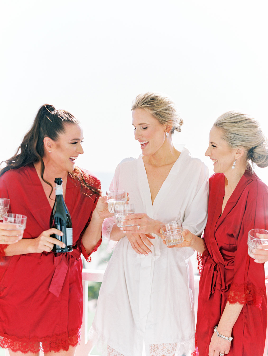 Bride in white robe sipping champagne with bridesmaids in burgundy robes. Hotel Del Coronado Wedding on film by Cavin Elizabeth.