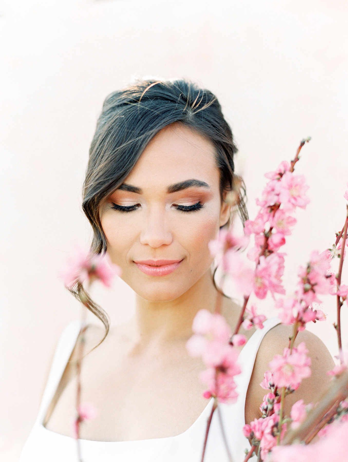 Bridal makeup with updo and some curls hanging down. Shot through pink flowers. Cavin Elizabeth Photography.