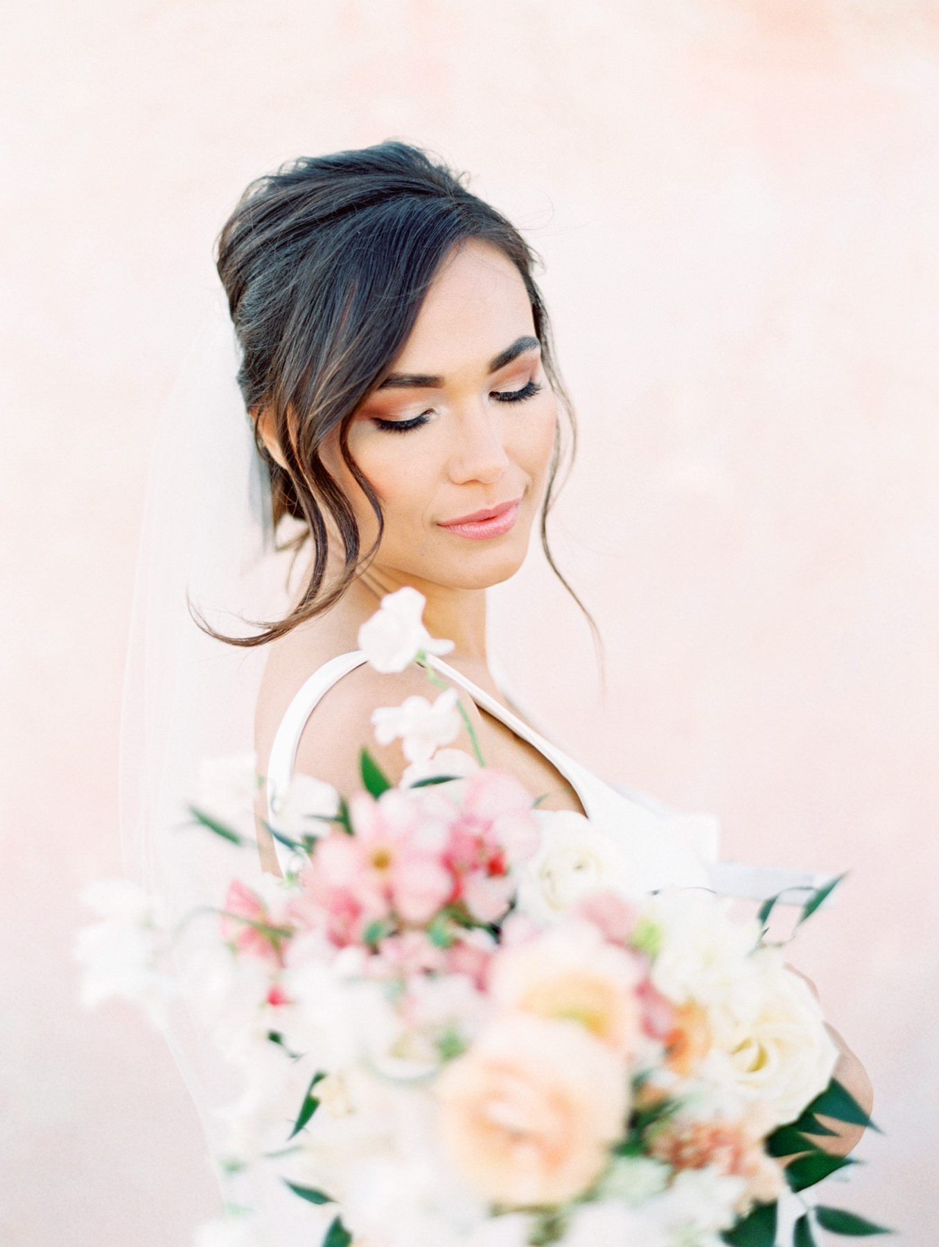Bouquet with pink and ivory roses, sweet peas, ranunculus, carnations, and greenery with a pink painterly backdrop. Martina Liana 1235 crepe square neck fit to flare gown from The White Flower. Fine art bridal curled updo. Cavin Elizabeth Photography - film photographer in San Diego.
