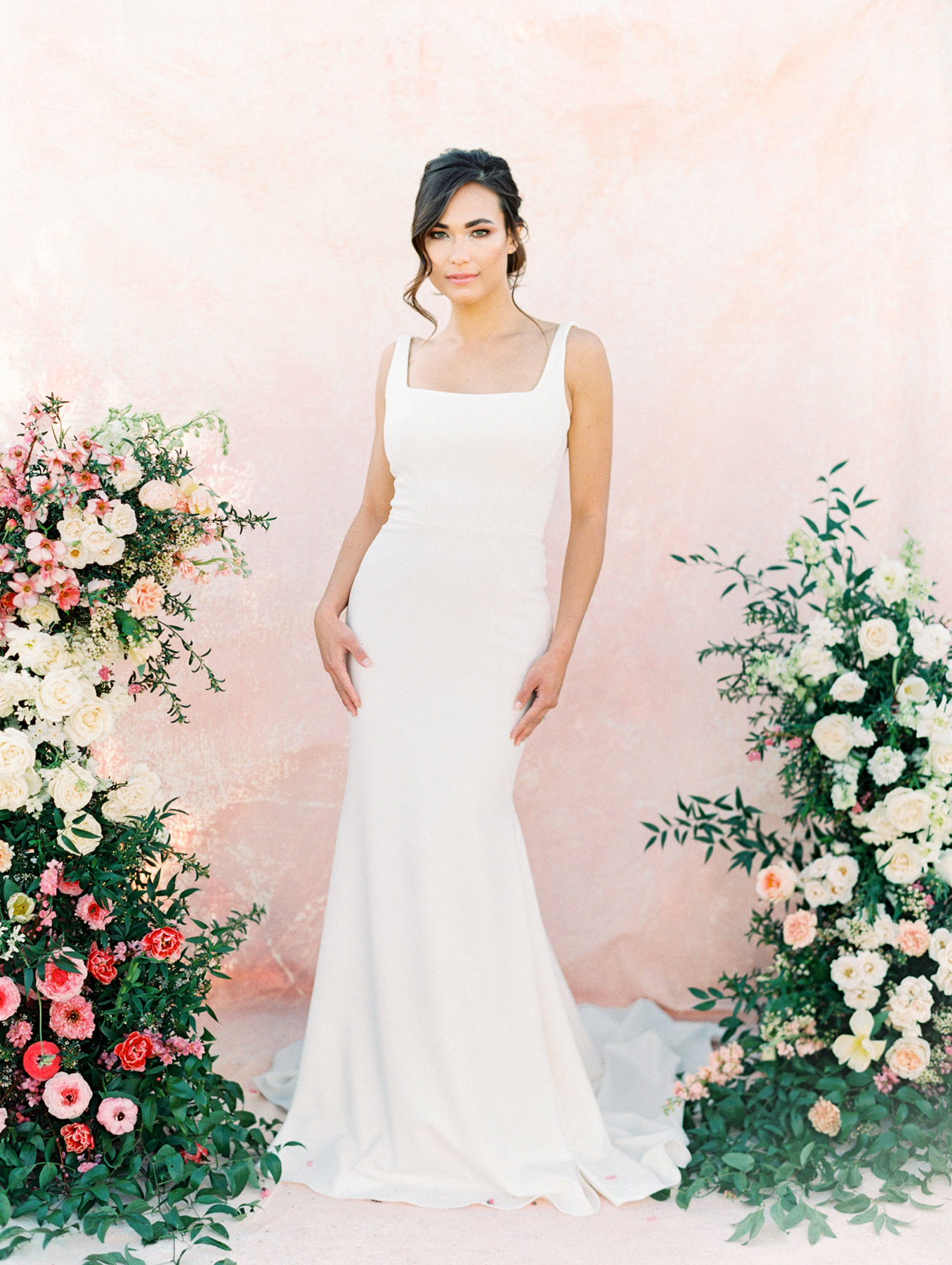 Asymmetrical floral arch with pink and ivory roses, sweet peas, ranunculus, carnations, and greenery with a pink painterly backdrop. Martina Liana 1235 crepe square neck fit to flare gown from The White Flower. Fine art bridal curled updo. Cavin Elizabeth Photography - film photographer in San Diego.