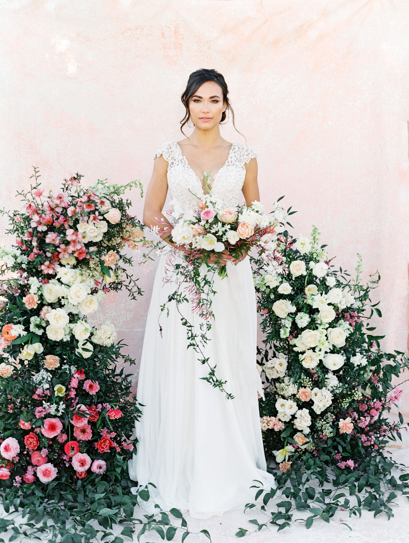 Asymmetrical floral arch with pink and ivory roses, sweet peas, ranunculus, carnations, and greenery with a pink painterly backdrop. Ivory pearl and opal beaded cap sleeve gown, plunging sweetheart neckline with illusion net insert and side cut outs, draped chiffon A-line skirt with slit. Hayley Paige Finley gown from The White Flower. Cavin Elizabeth Photography - film photographer in San Diego.
