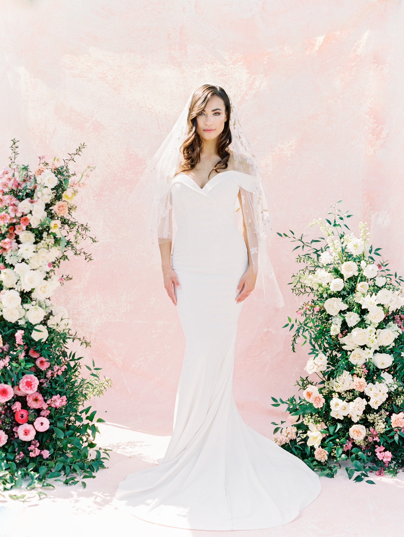 Bouquet and asymmetrical floral arch with pink and ivory roses, sweet peas, ranunculus, carnations, and greenery with a pink painterly backdrop. Twigs and Honey gold floral embellished veil paired with Kelly Faetanini crepe sweetheart neck off the shoulder fit to flare gown from The White Flower. Cavin Elizabeth Photography - film photographer in San Diego.