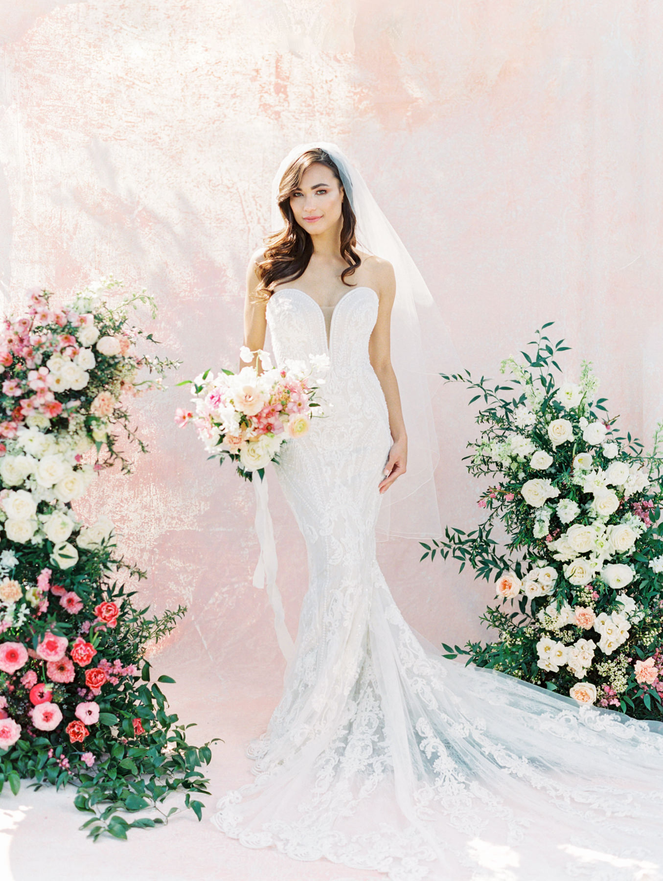 Bouquet and asymmetrical floral arch with pink and ivory roses, sweet peas, ranunculus, carnations, and greenery with a pink painterly backdrop. Martina Liana 1060 beaded strapless fit-and-flare lace gown from The White Flower. Cavin Elizabeth Photography - film photographer.