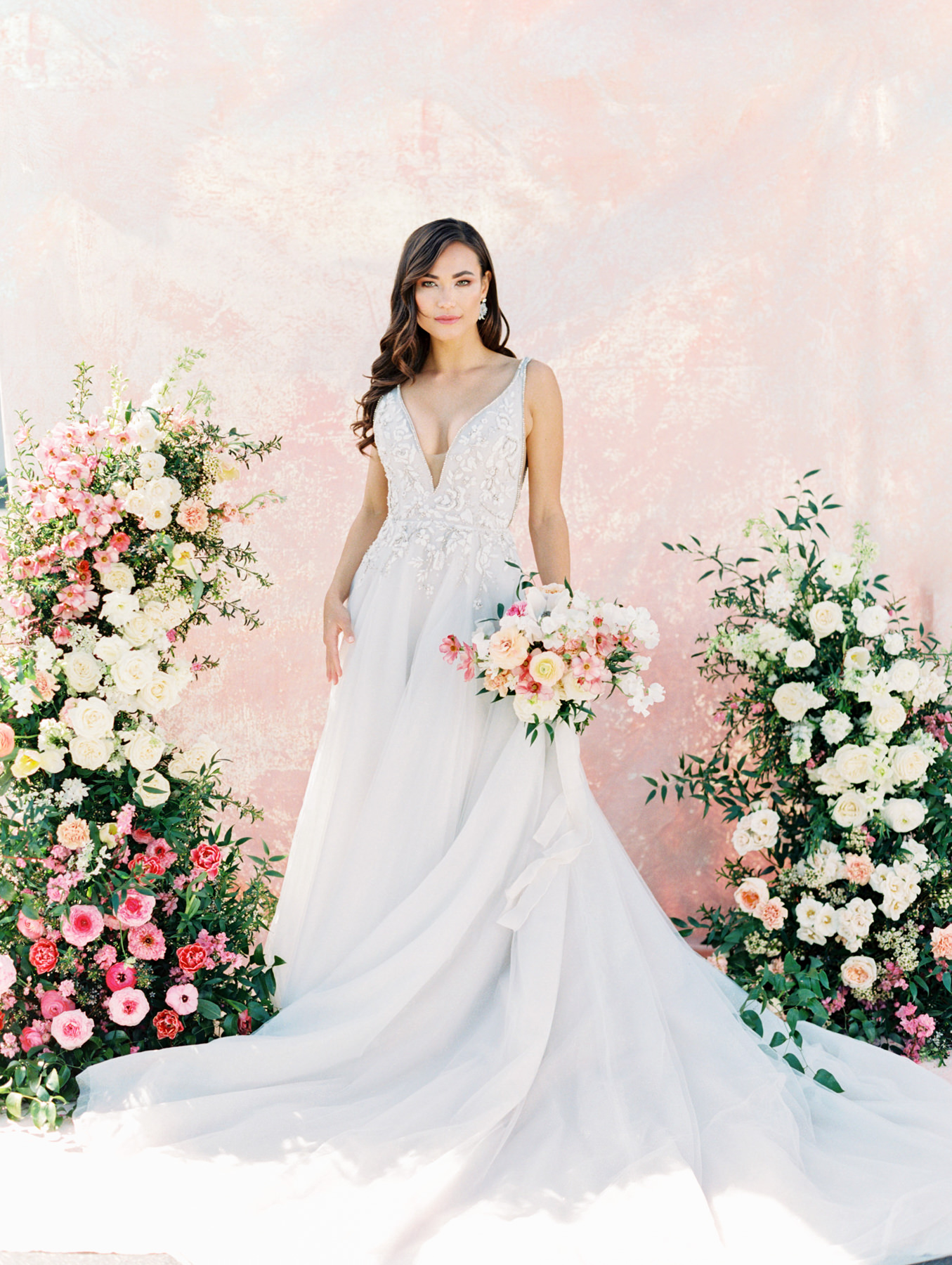 Asymmetrical floral arrangement with pink and ivory roses, sweet peas, ranunculus, carnations, and greenery with a pink painterly backdrop. Bridal bouquet with ivory, pink, peach, carnations, roses, ranunculus, sweet peas, and greenery. Haiku beaded and embroidered A-line gown, plunging V-neckline with illusion net insert and side cut outs, low scoop back and rhinestone trim, full skirt with layered starlight sparkle tulle. Hayley Paige Lauren gown from The White Flower. Cavin Elizabeth Photography - film photographer in San Diego.