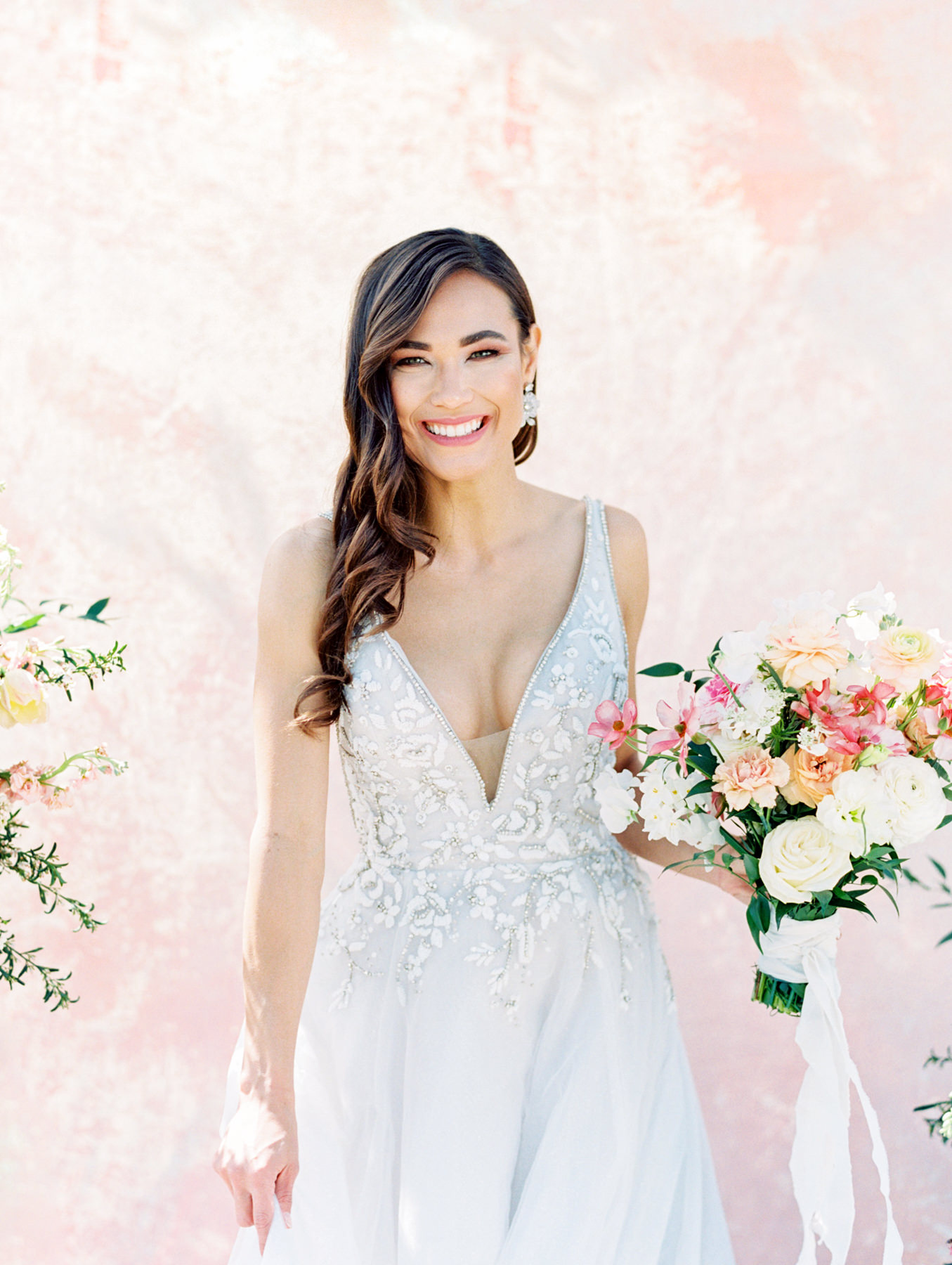 Bridal bouquet with ivory, pink, peach, carnations, roses, ranunculus, sweet peas, and greenery. Haiku beaded and embroidered A-line gown, plunging V-neckline with illusion net insert and side cut outs, low scoop back and rhinestone trim, full skirt with layered starlight sparkle tulle. Hayley Paige Lauren gown from The White Flower. Cavin Elizabeth Photography - film photographer in San Diego.