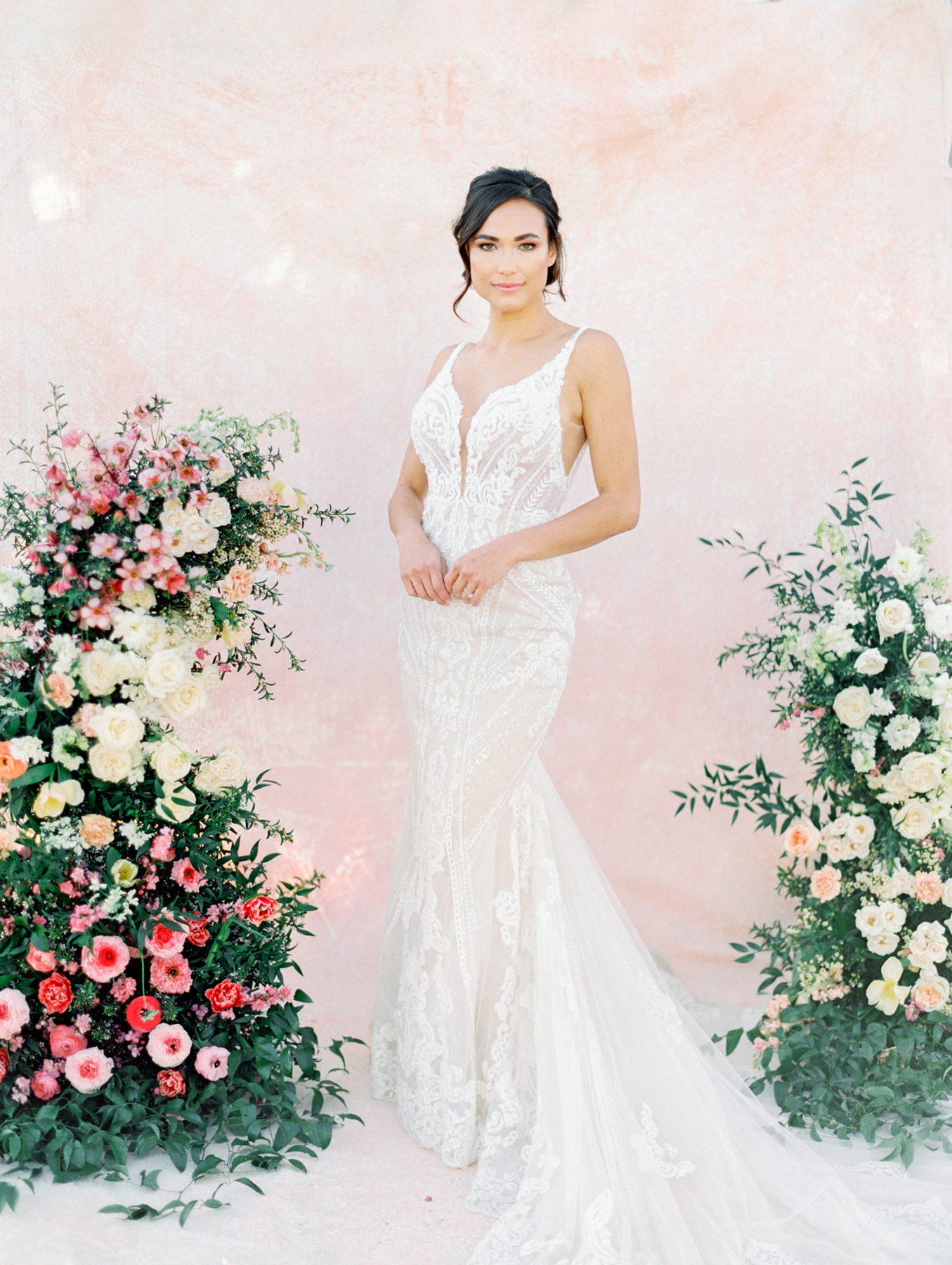 Asymmetrical floral arrangement with pink and ivory roses, sweet peas, ranunculus, carnations, and greenery with a pink painterly backdrop. Martina Liana 1066 beaded lace gown from The White Flower. Cavin Elizabeth Photography - film photographer in San Diego.