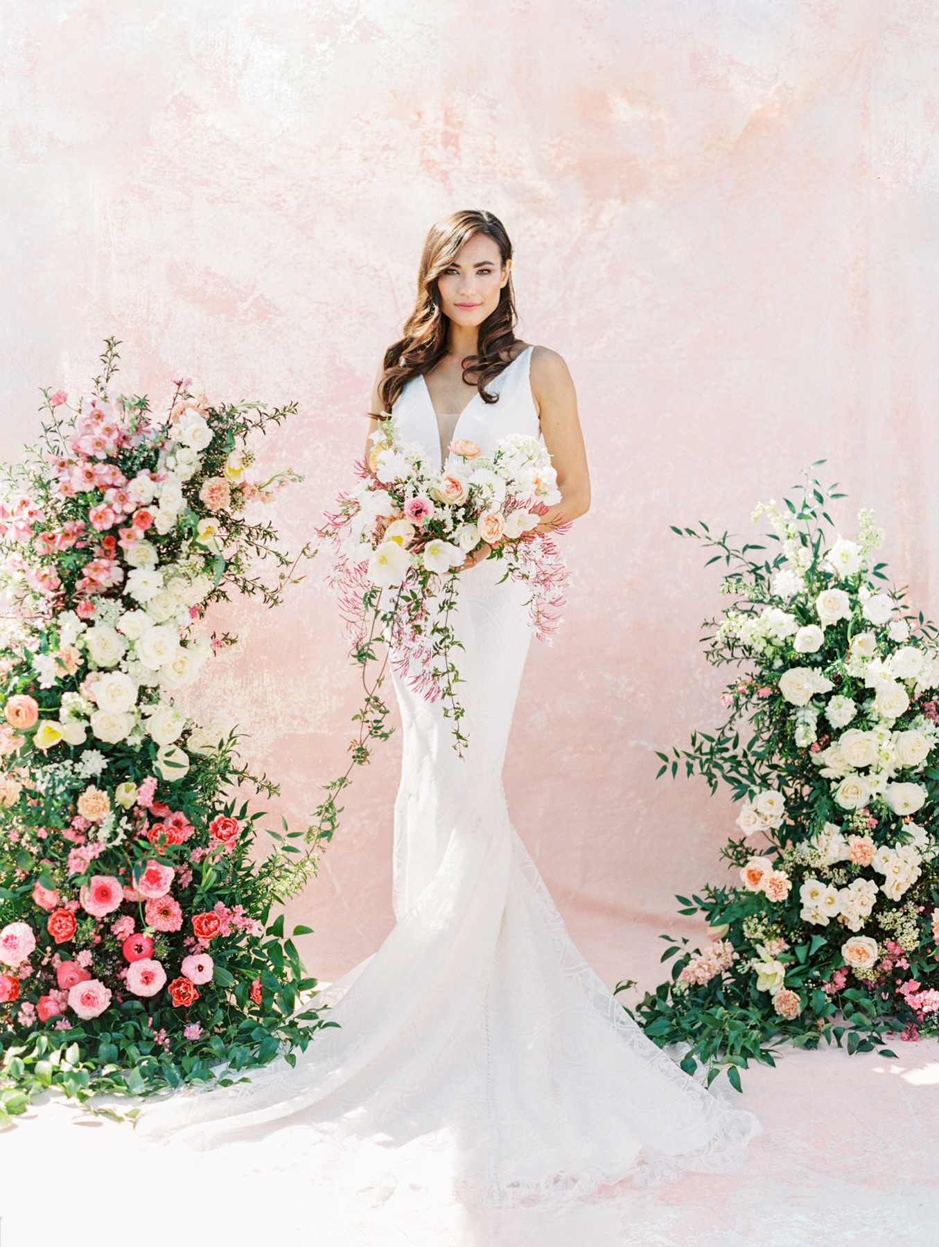 Wild long bridal bouquet and asymmetrical floral arch with pink and ivory roses, sweet peas, ranunculus, carnations, and greenery with a pink painterly backdrop. Kelly Faetanini Ariana (fashion-grade Neoprene and lace fit-to-flare wedding dress is destination wedding-approved. With a delicate lace and flattering plunging V neckline silhouette and low back) gown from The White Flower. Hair down and curled with hair vine. Kelly Faetanini Wedding Dresses in San Diego. Cavin Elizabeth Photography.