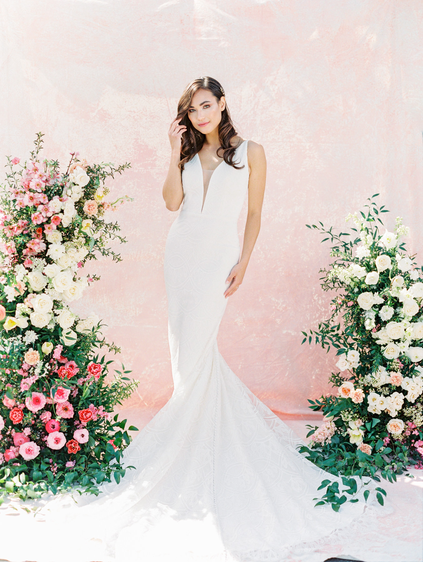 Asymmetrical floral arch with pink and ivory roses, sweet peas, ranunculus, carnations, and greenery with a pink painterly backdrop. Kelly Faetanini Ariana (fashion-grade Neoprene and lace fit-to-flare wedding dress is destination wedding-approved. With a delicate lace and flattering plunging V neckline silhouette and low back) gown from The White Flower. Hair down and curled with hair vine. Cavin Elizabeth Photography - film photographer in San Diego.