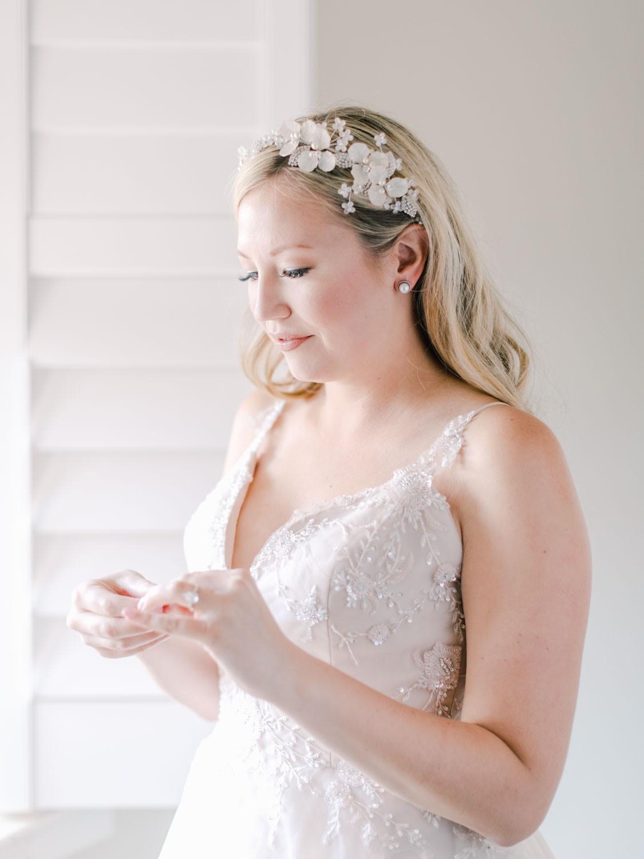Bride putting on earrings. Film photography at Jekyll Island Club Resort Wedding by Cavin Elizabeth Photography