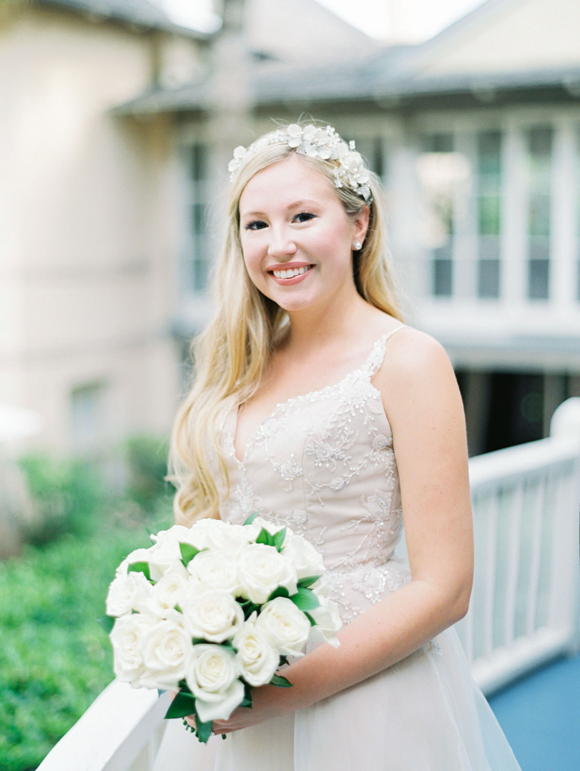 Bride in a champagne gown with a floral tiara headband and all white rose bouquet with greenery. Film photography at Jekyll Island Club Resort Wedding by Cavin Elizabeth Photography