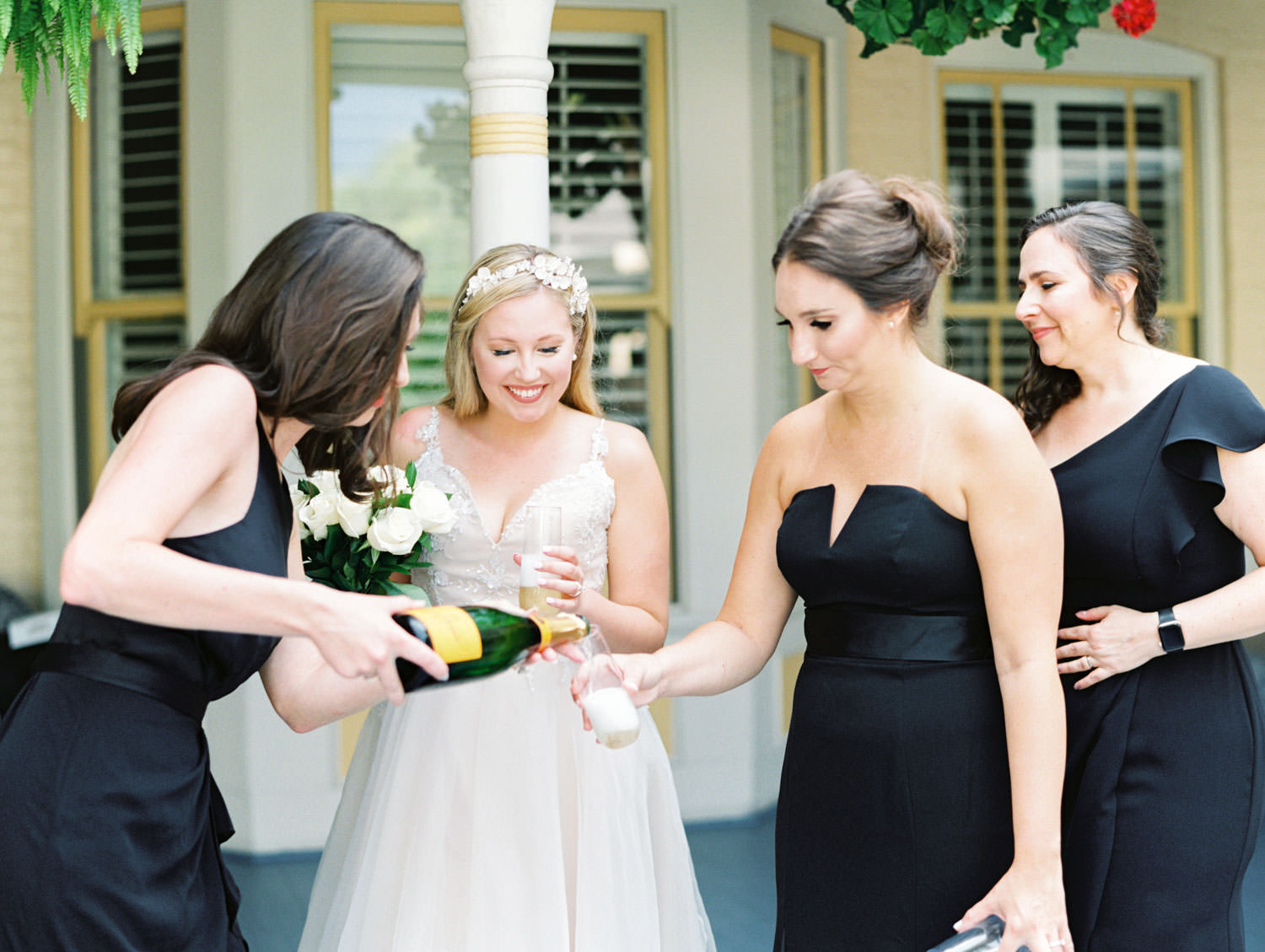 Bride in a champagne gown with a floral tiara headband pouring champagne with bridesmaids in formal black gowns. Film photography at Jekyll Island Club Resort Wedding by Cavin Elizabeth Photography