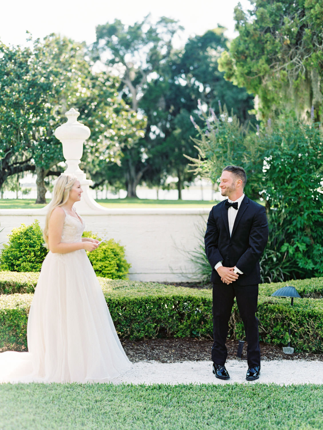 Bride in a champagne gown with a floral tiara headband first look with groom in black tuxedo. Film photography at Jekyll Island Club Resort Wedding by Cavin Elizabeth Photography