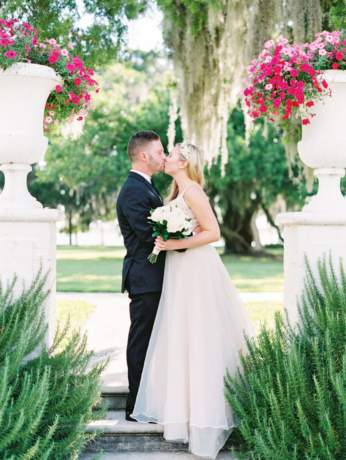 Bride in a champagne gown with a floral tiara headband private vow reading with groom in black tuxedo. Film photography at Jekyll Island Club Resort Wedding by Cavin Elizabeth Photography