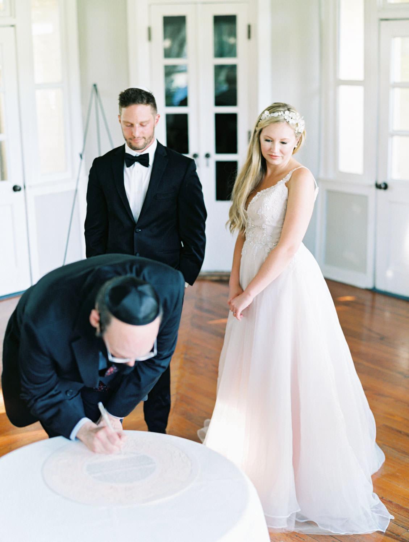 Intimate ketubah signing. Film photography at Jekyll Island Club Resort Wedding by Cavin Elizabeth Photography