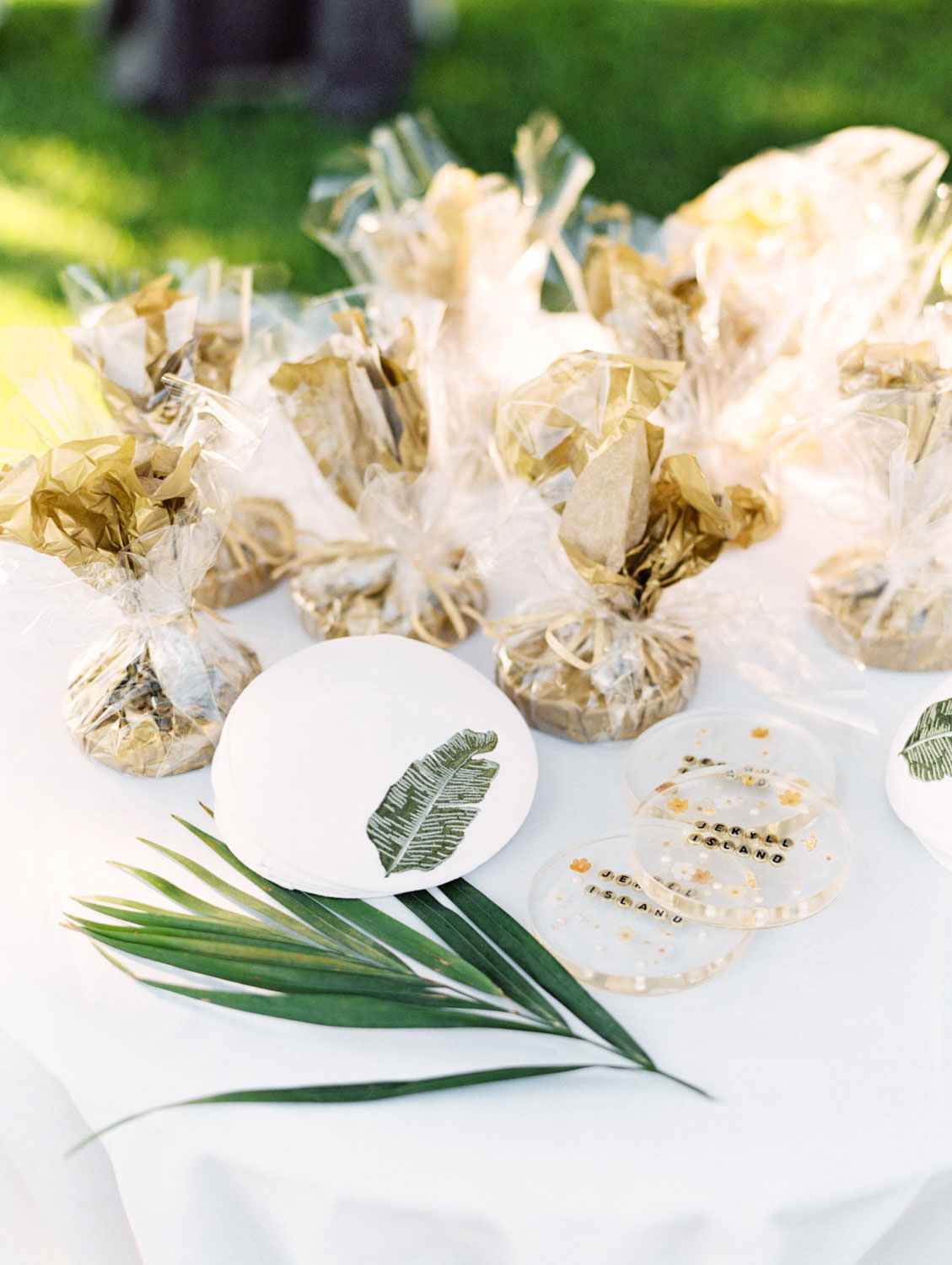 Ceremony favors for guests with white yarmulke with a banana leaf embroidered and custom acrylic drink coasters. Film photography at Jekyll Island Club Resort Wedding by Cavin Elizabeth Photography