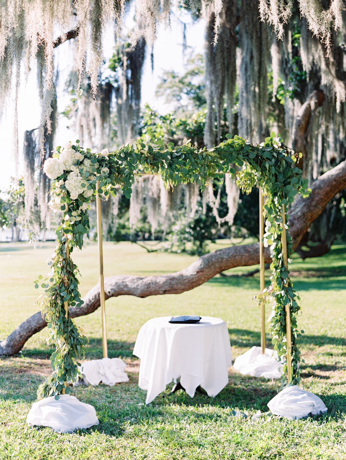 Chuppah covered in silver dollar eucalyptus and white flowers under a tree covered in spanish moss. Film photography at Jekyll Island Club Resort Wedding by Cavin Elizabeth Photography