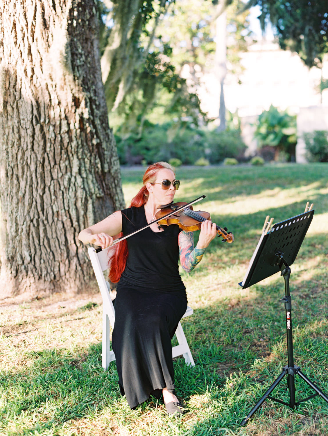 Single violinist under a tree covered in spanish moss. Film photography at Jekyll Island Club Resort Wedding by Cavin Elizabeth Photography