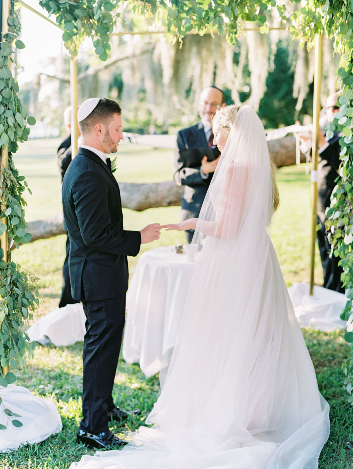 Micro wedding with 21 guests. Chuppah covered in silver dollar eucalyptus and white flowers under a tree covered in spanish moss. Film photography at Jekyll Island Club Resort Wedding by Cavin Elizabeth Photography