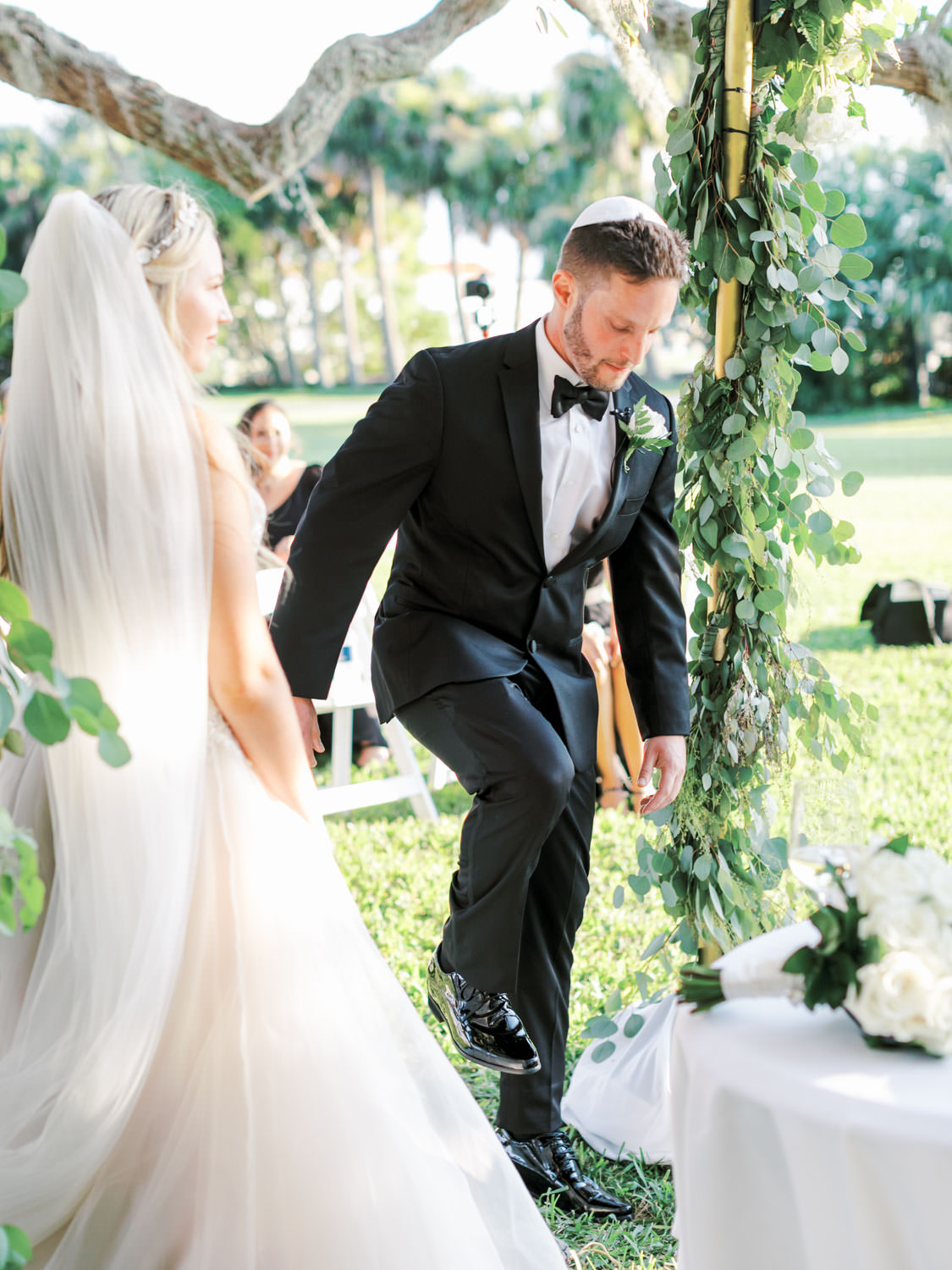 Groom breaking the glass. Chuppah covered in silver dollar eucalyptus and white flowers under a tree covered in spanish moss. Film photography at Jekyll Island Club Resort Wedding by Cavin Elizabeth Photography