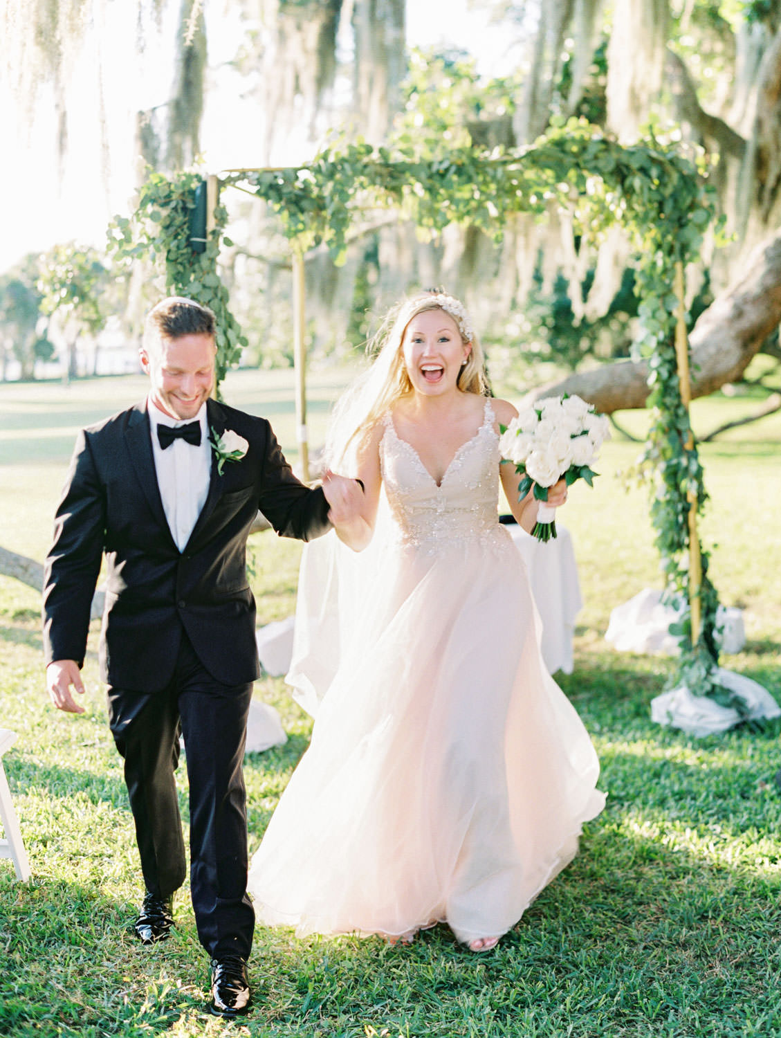 Bride and groom running down the aisle. Chuppah covered in silver dollar eucalyptus and white flowers under a tree covered in spanish moss. Film photography at Jekyll Island Club Resort Wedding by Cavin Elizabeth Photography