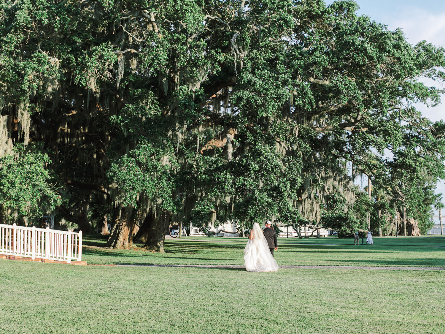 Bride and groom walking privately after the ceremony. Chuppah covered in silver dollar eucalyptus and white flowers under a tree covered in spanish moss. Film photography at Jekyll Island Club Resort Wedding by Cavin Elizabeth Photography