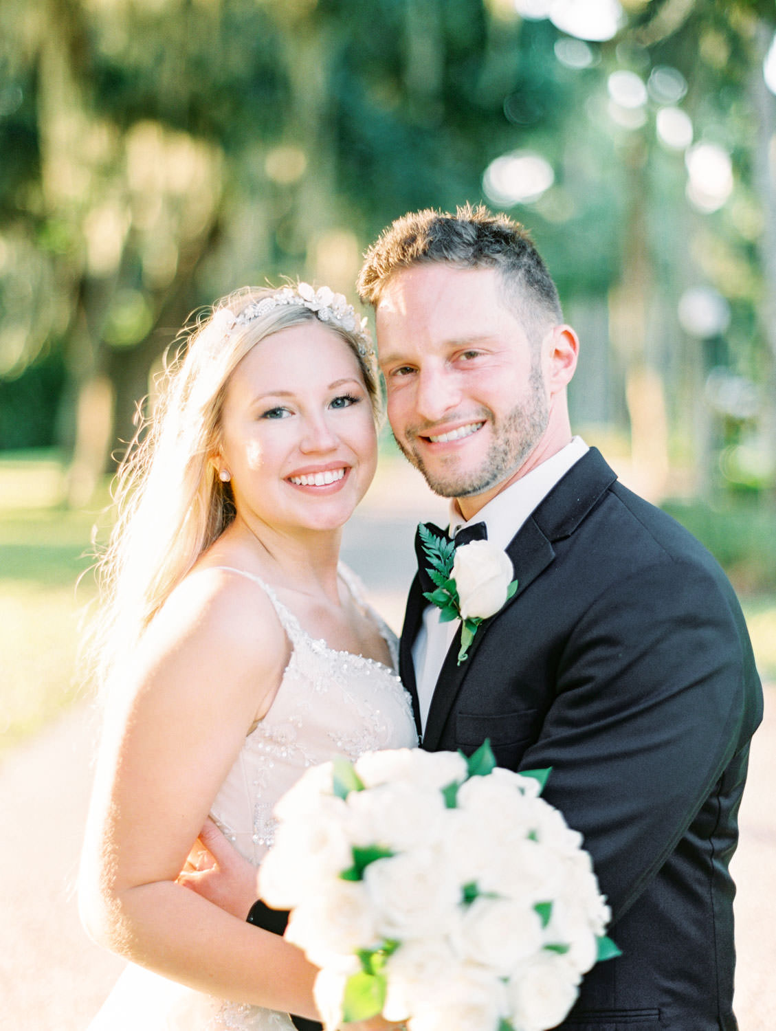 Bride in a champagne gown with a floral tiara headband with groom in black tuxedo. Film photography at Jekyll Island Club Resort Wedding by Cavin Elizabeth Photography