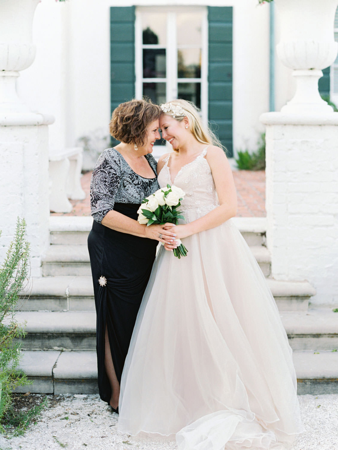Bride in a champagne gown with a floral tiara headband with her mother. Film photography at Jekyll Island Club Resort Wedding by Cavin Elizabeth Photography