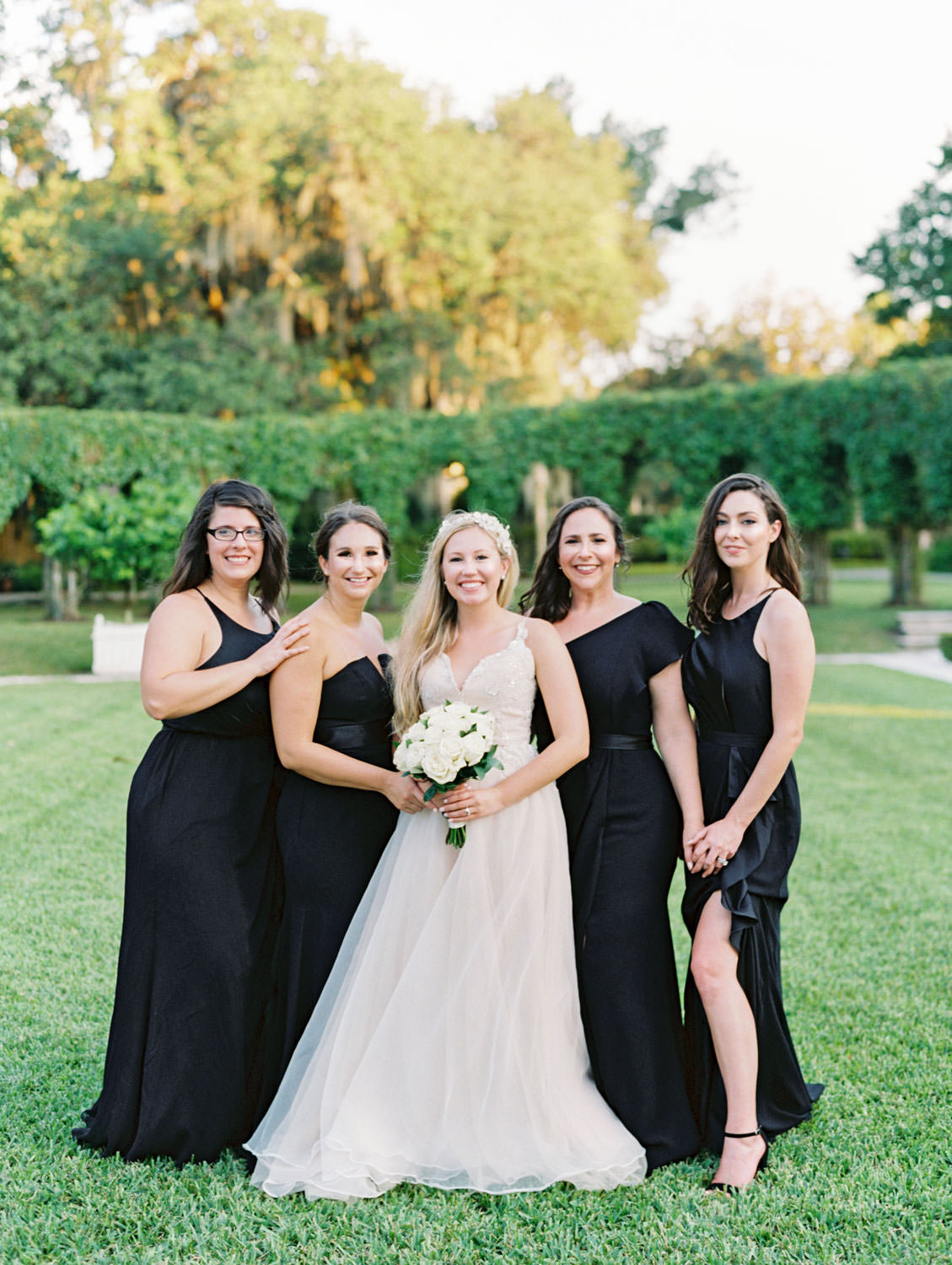 Bride in a champagne gown with a floral tiara headband with her bridesmaids in formal black gowns. Film photography at Jekyll Island Club Resort Wedding by Cavin Elizabeth Photography