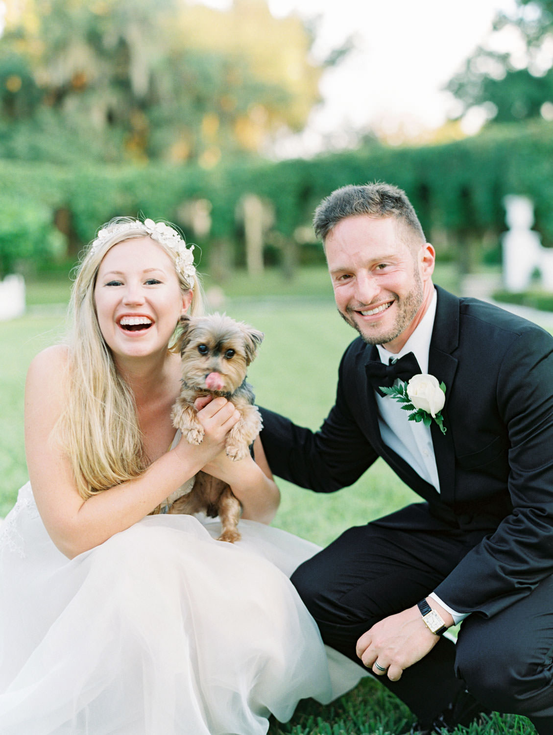 Bride in a champagne gown with a floral tiara headband with groom in black tuxedo and their teacup yorkie. Film photography at Jekyll Island Club Resort Wedding by Cavin Elizabeth Photography