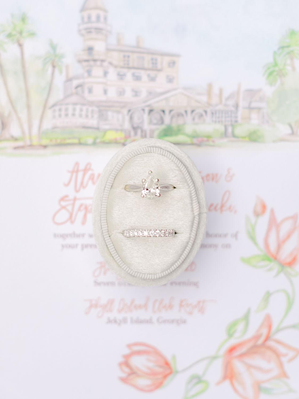 Bride's wedding rings in a velvet oval ring box on top of custom venue illustration wedding invitation. Wedding film photography at Jekyll Island Club Resort by Cavin Elizabeth Photography
