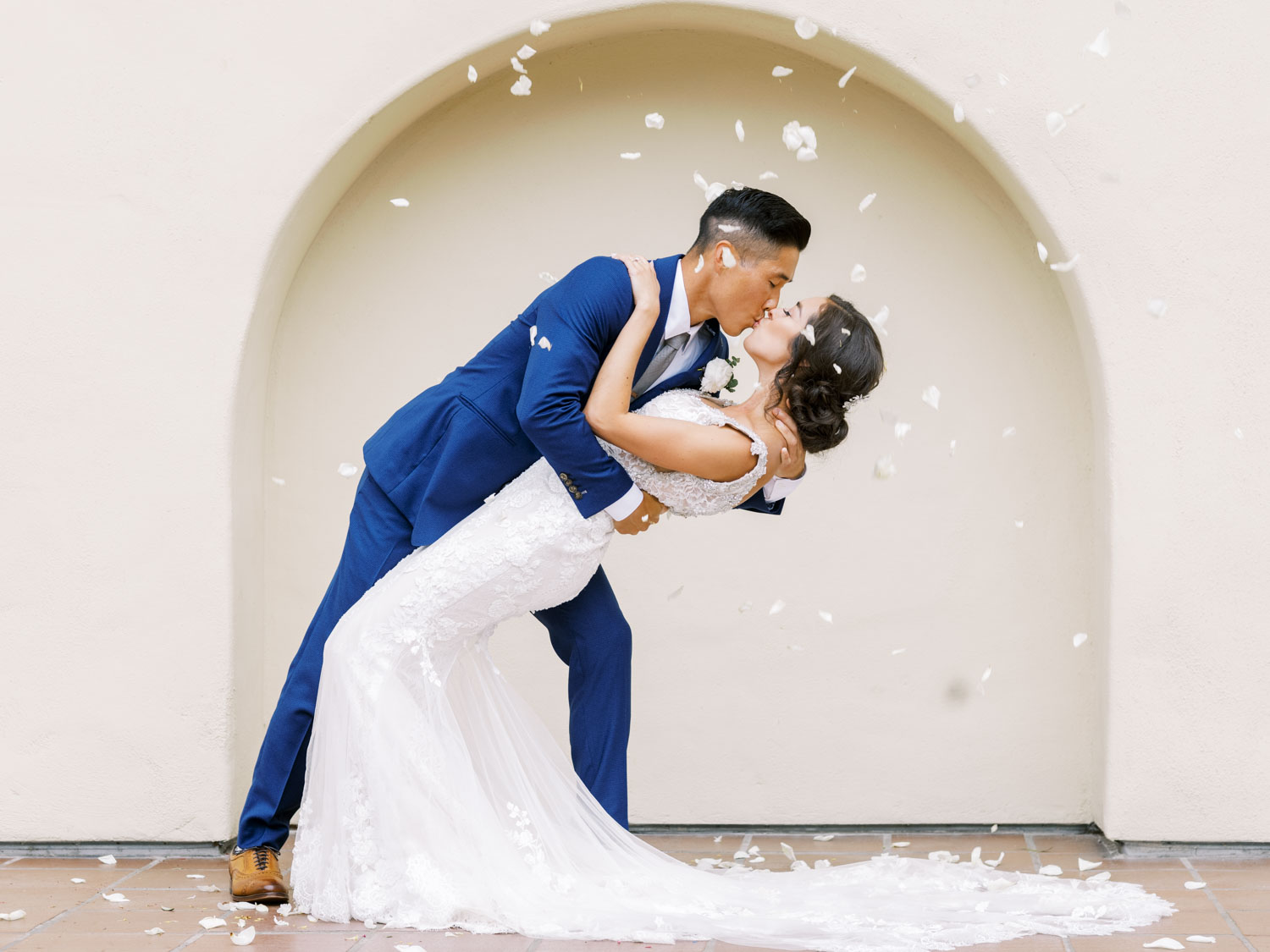 Bridal party tossing rose petals from above onto the bride and groom kissing. Cavin Elizabeth Photography